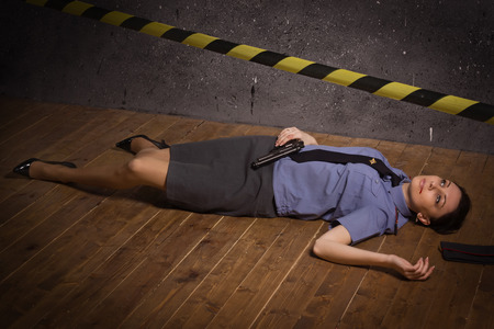 Crime scene imitation. Woman police officer lying on a floor