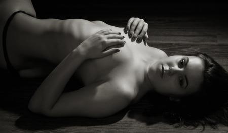 femme nu sexy: Belle femme sexy nue couch�e sur le sol. Low key, en niveaux de gris. Banque d'images