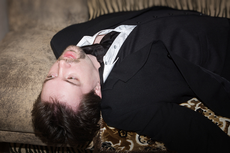 swooned: Corpse of business man lays on a sofa