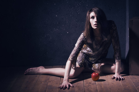 sanitarium: Asylum. Lonely mad woman with red apple sitting on a floor. Low key.