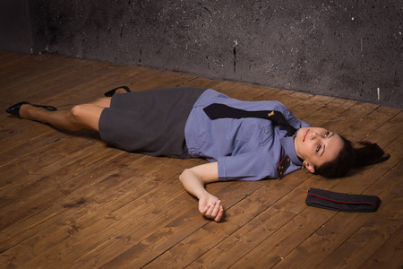 corpse: Crime scene imitation. Woman police officer lying on a floor