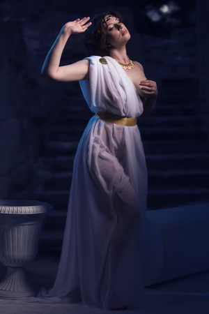 toga: Godness antigua en blanco toga grecia sobre un fondo ruinas del templo. Luces de la noche.