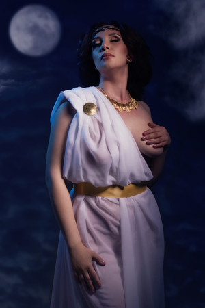 Beautiful Woman Wearing White Greek Toga on a dark background