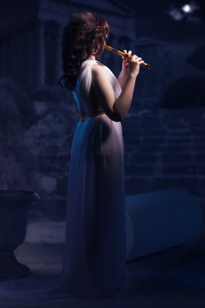 voluptuous women: Ancient godness in a white greece toga playing the flute on a temple ruins background. Night lights. Stock Photo