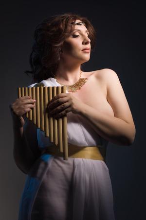 toga: Mujer hermosa que desgasta blanca toga griega con la flauta en un fondo oscuro Foto de archivo