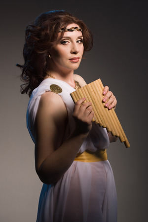 toga: Beautiful woman wearing white greek toga with flute on a dark background Stock Photo