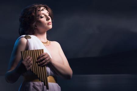 toga: Godness antiguo en una grecia blanca toga con la flauta. Luces de la noche. Foto de archivo