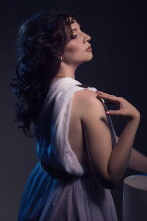toga: Beautiful Woman Wearing White Greek Toga on a dark background