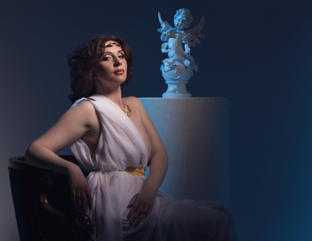toga: Mujer hermosa que desgasta blanca griega Toga en un interior antiguo oscuro