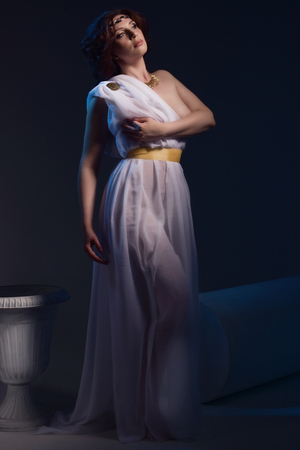 toga: Mujer hermosa que desgasta blanca griega Toga sobre un fondo oscuro