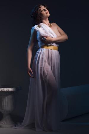 Schöne Frau, die weiße griechische Toga auf einem dunklen Hintergrund Standard-Bild - 40654580
