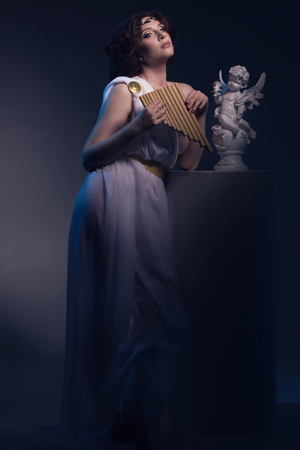 ancient sexy: Ancient godness in a white greece toga with the flute. Night lights. Stock Photo