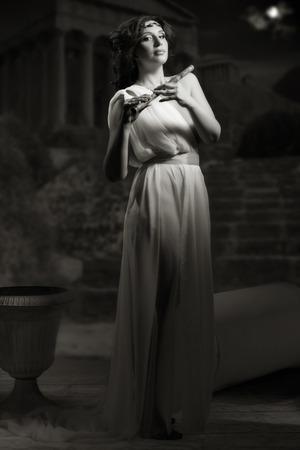 toga: Godness antiguo en una grecia blanca toga que toca la flauta en un fondo ruinas del templo. Luces de la noche. Foto de archivo