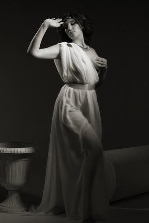 voluptuous women: Beautiful Woman Wearing White Greek Toga on a dark background