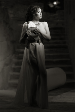toga: Godness antigua en blanco toga grecia sobre un fondo ruinas del templo. Luces de la noche, en escala de grises