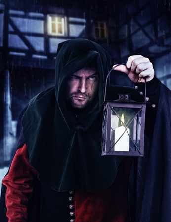 medieval: Vigilante nocturno en un traje medieval y capucha con una linterna