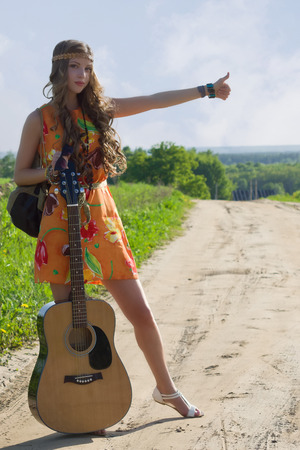her: Romantic girl travelling with her guitar. Hippie style.