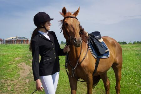 equitation: Beautiful young girl jockey talks with her horse dressing uniform competition