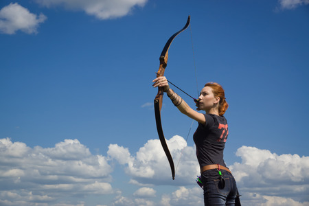 bow and arrow: Archery woman bends bow archer target narrow in the summer field