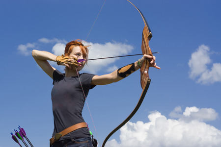 practice: Archery woman bends bow archer target narrow in the summer field