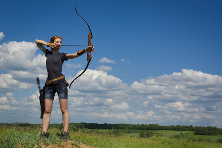 aiming: Archery woman bends bow archer target narrow in the summer field