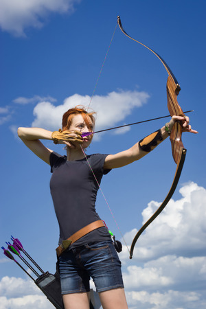 Archery woman bends bow archer target narrow in the summer field 版權商用圖片 - 43943831