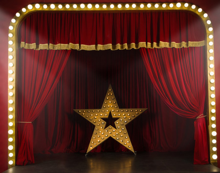 at the theater: Theater stage with red curtains and spotlights. Theatrical scene in the light of searchlights Stock Photo