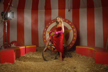 actress: Circus actress in a red dress on retro bike Stock Photo