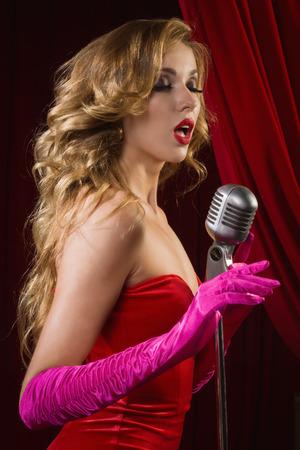 female singer: Retro female singer sing holding vintage microphone