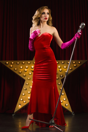 singer on stage: Retro female singer sing holding vintage microphone