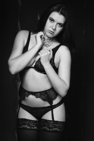 subjugation:   brunette in chains. Black and white image, low key