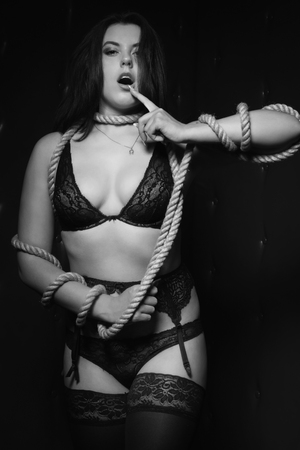 brunette with hands bound in a dark room. Black and white image, low key