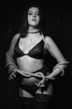 subjugation:   brunette with hands bound in a dark room. Black and white image, low key