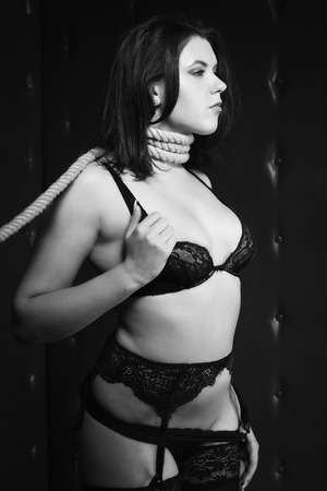 subjugation:   brunette with the noose around her neck. Black and white image, low key