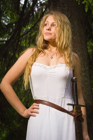valkyrie: Beautiful blond woman in white dress with sword in a wild forest Stock Photo