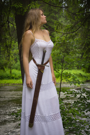 Beautiful blond woman in white dress with sword in a wild forest Stock Photo