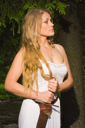 valkyrie: Beautiful young girl in white dress holding a medieval sword