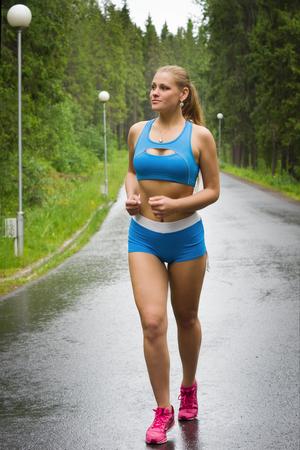 hacer footing: Hermosa niña feliz corriendo en el parque verde en día de verano lluviosa