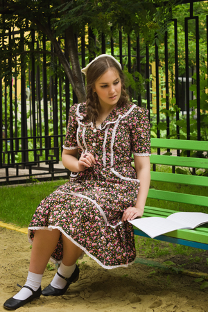 music book: Very beautiful soviet girl in retro style with a music book sitting on a bench in the park Stock Photo