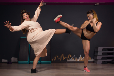 mujeres gordas: Muchacha atlética que luchan con las mujeres gordas. Mismo modelo Foto de archivo