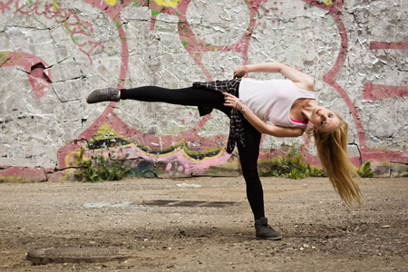 Young girl dancing on graffiti background. Dancing and urban culture concept. Stock Photo