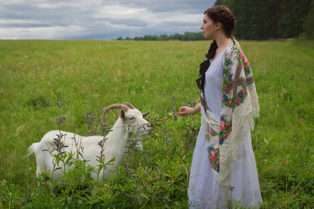 herding: Russian woman in traditional clothes herding goats Stock Photo