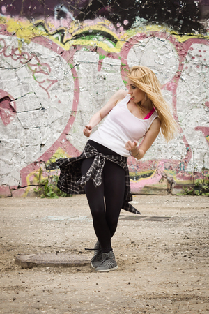 urban culture: Young girl dancing on graffiti background. Dancing and urban culture concept. Stock Photo