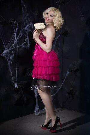 dark interior: young woman in dolls dress in a dark interior