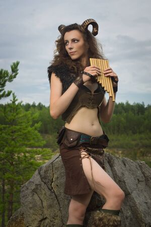 mythological: Pretty female faun in a wood. Woman with a mythological creature playing flute