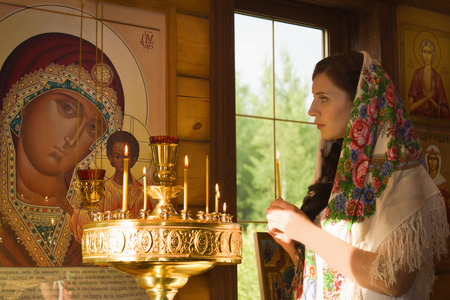 people in church: Russian woman with candles in Orthodox Russian Church