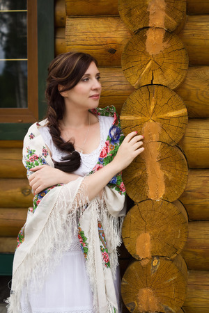 traditional clothes: Russian woman in traditional clothes on background of the hut