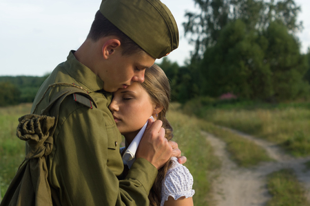 Soviet soldier in uniform of World War II saying goodbye to girl