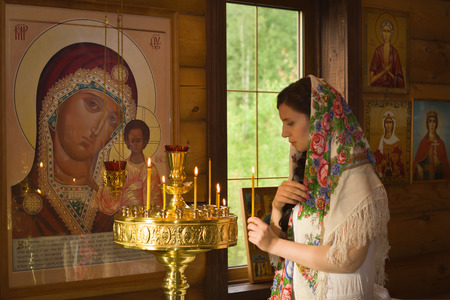 family church: Russian woman with candles in Orthodox Russian Church