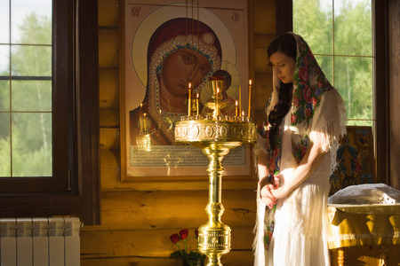 family indoors: Russian woman with candles in Orthodox Russian Church